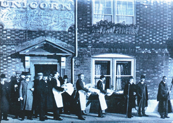 Carrying Christmas food to ladies in the Almshouses. Early 1900's