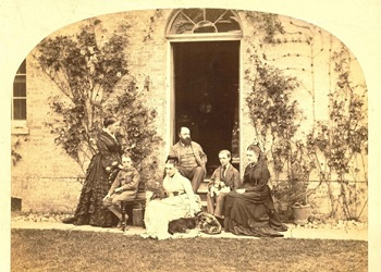 C. T. Halsted, founder of the ironworks, sitting outside his house (centre) with his family and dogs