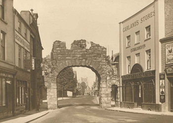 A view of Eastgate Square with an arch built for the Coronation of George V in 1911. Sharp Garland's grocers can be seen to the right, and the Market Cross and bell tower can be seen through the arch