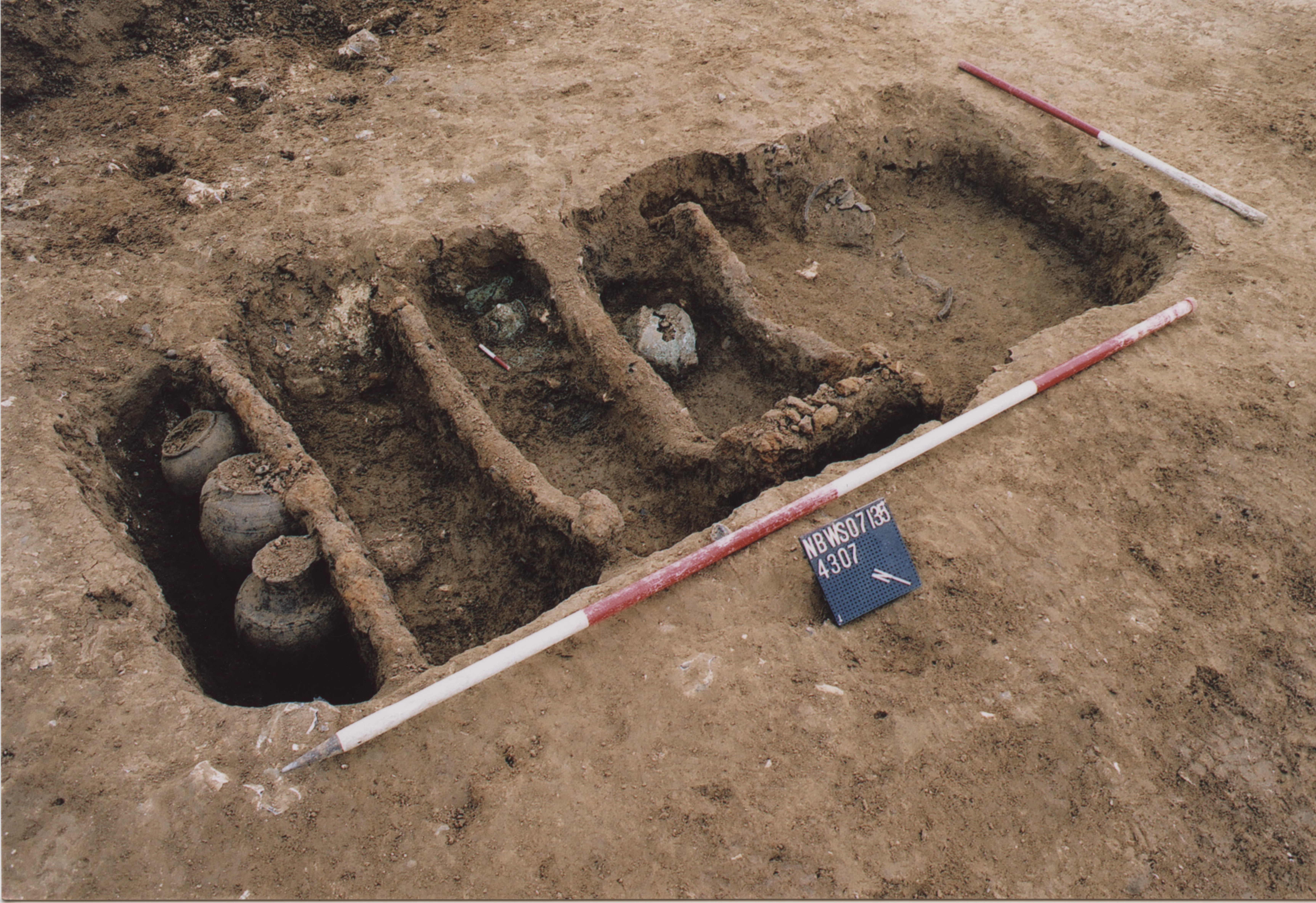 The Mystery Warrior's grave, part was through excavation. Just visible are the shield boss and helmet. Image courtesy of Thames Valley Archaeological Services Ltd
