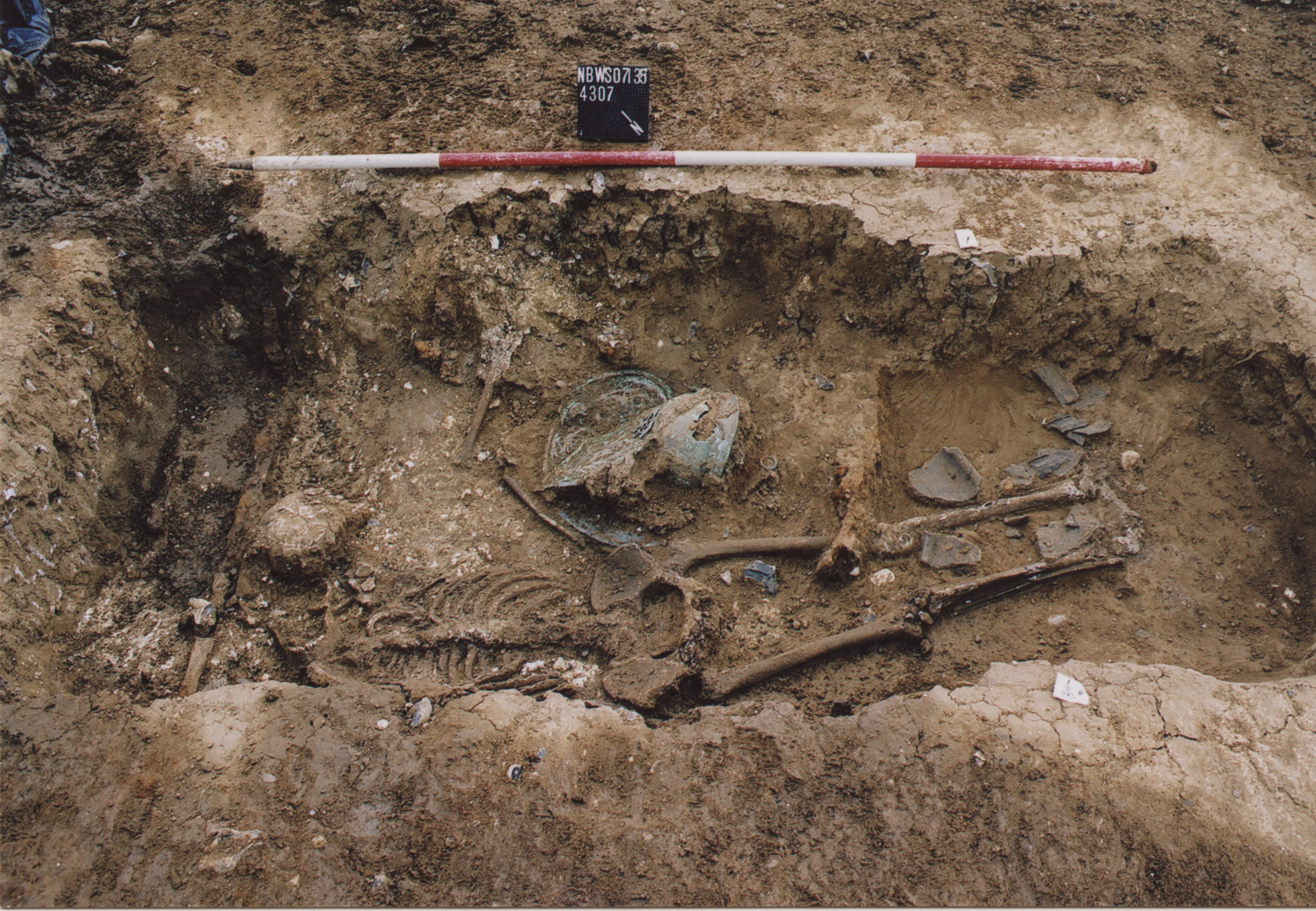 Further into the excavation of the grave the human remains are now visible, as is the incredible openwork crests adorning the helmet. Image courtesy of Thames Valley Archaeological Services Ltd